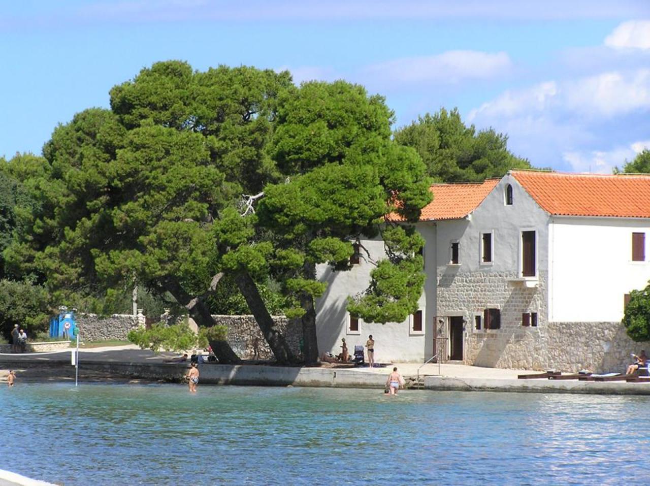 U mjestu Ugljanu uz pješčanu plažu Mostir već su gotovo šest stoljeća franjevački samostan i crkva sv. Jeronima koje je kao obiteljsku zadužbinu 1430. godine utemeljio Šimun Benja, djed modruškoga biskupa Šimuna Kožičića Benje.